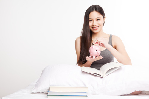 A shot of a beautiful asian college student reading on her bed